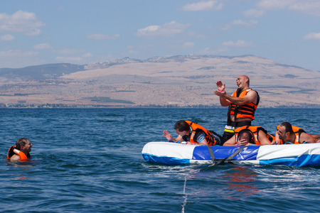 Tiberias, Israel, September 27, 2016: Group of young men floating on an inflatable attraction on Lake Kinneret in Tiberias, Israel