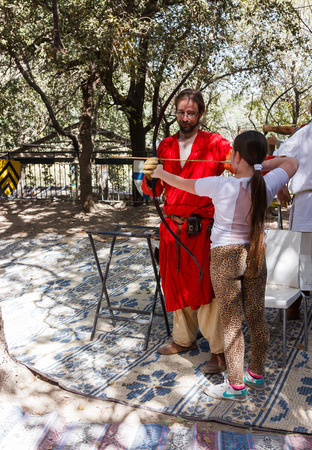 teaches: Jerusalem, Israel, October 03, 2016: Member of the annual festival of Knights of Jerusalem, teaches a girl to shoot a bow in Jerusalem, Israel