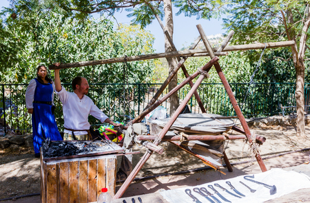 medieval blacksmith: Jerusalem, Israel, October 03, 2016: Member of the annual festival of Knights of Jerusalem, dressed as a blacksmith blows ancillary fur in Jerusalem, Israel