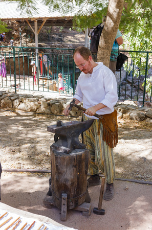 medieval blacksmith: Jerusalem, Israel, October 03, 2016: Member of the annual festival of Knights of Jerusalem, dressed as a blacksmith forges iron detail in Jerusalem, Israel