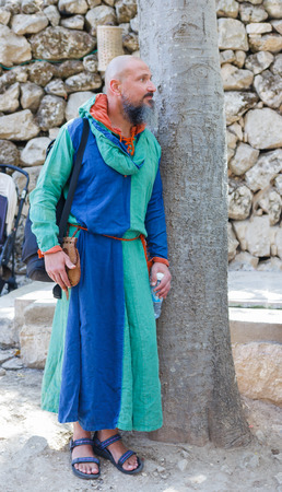 Jerusalem, Israel, October 03, 2016: Member of the annual festival of Knights of Jerusalem, resting near a tree in Jerusalem, Israel