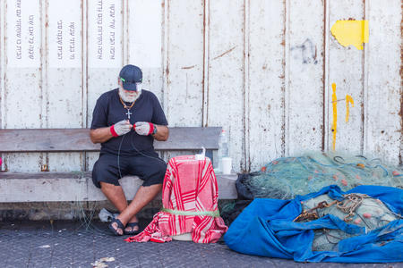 yafo: Yafo, Israel, October 15, 2016: Elderly fisherman sits on the waterfront and repairing fishing net in Yafo, Israel Editorial