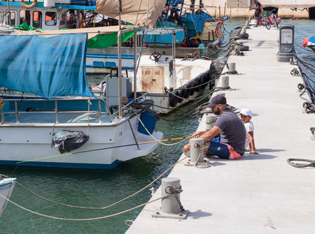 yafo: Yafo, Israel, October 15, 2016: Father and son fishing on the waterfront in Yafo, Israel