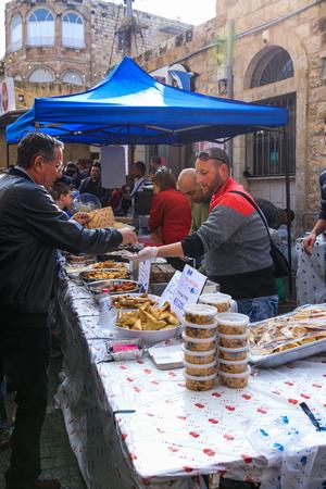 lebanese food: Haifa, Israel - December 17, 2016: Seller of Lebanese food sells to customers at the Christmas market in the German Colony in Haifa, Israel Editorial