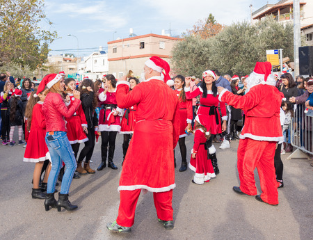 Miilya, Israel - December 23, 2016 : The group of Santa Clauses entertains participants of the annual Christmas run in the village in Miilya, Israel