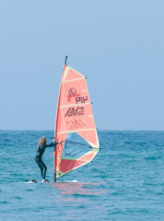 Nahariya, Israel - January 07, 2016 : Girl in a black tracksuit exercising in windsurfing in the Mediterranean sea in Nahariya, Israel