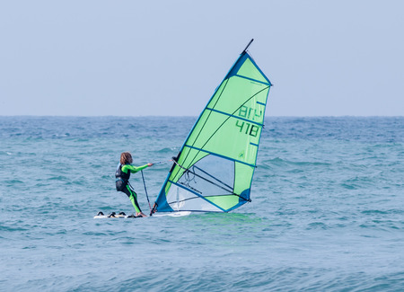 Nahariya, Israel - January 07, 2016 : Girl in a color tracksuit exercising in windsurfing in the Mediterranean sea in Nahariya, Israel