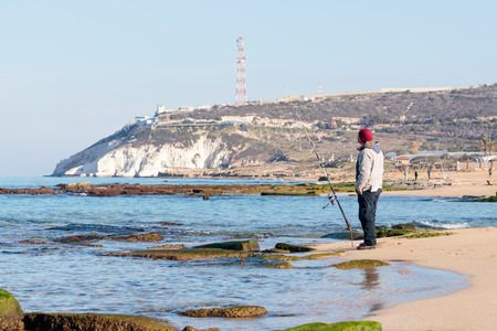 hanikra: Rosh Hanikra, Israel - February 04, 2017 : Fisherman catches a fish on a spinning at winter morning on the beach near the Rosh Hanikra, Israel