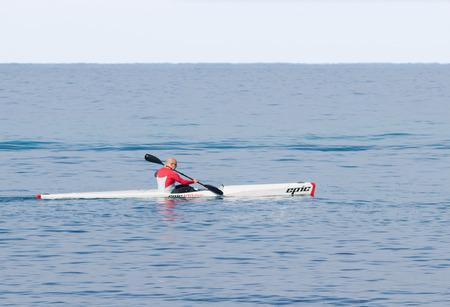 Nahariyya, Israel - February 04, 2017 : Athlete in color tracksuit  training on kayak winter morning on Mediterranean Sea near the coast of Nahariyya, Israel