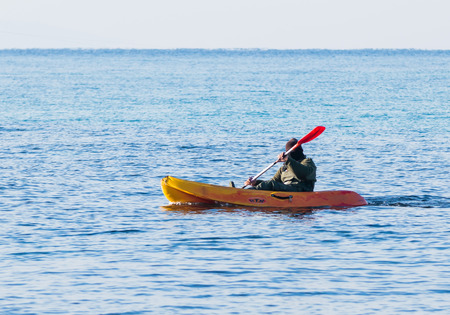 Nahariyya, Israel - February 04, 2017 : Fisherman in a green jumpsuit floats in orange kayak on the sea, near the coast of Nahariyya, Israel. Editorial