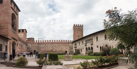 locality: Verona, Italy - September 26, 2015 : Tourists walking in the courtyard of the Castelvecchio Museum on a cloudy day, inspect the museum and take pictures in Verona, Italy.