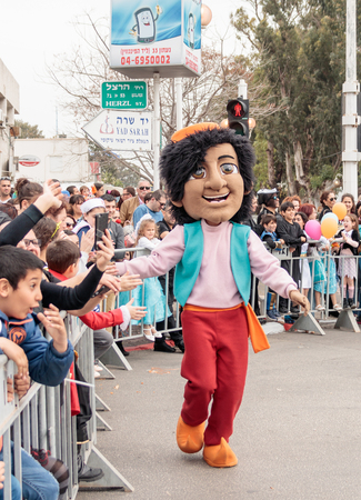 Nahariyya, Israel, March 10, 2017 : Participant in the traditional annual carnival parade Adloyada dressed in the suit of Aladdin goes near the viewers and gives them a hand in Nahariyya, Israel