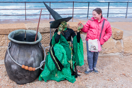 Caesarea, Israel, March 11, 2017 : Participant of the Purim festival dressed in a witch costume sits on the embankment and gives the girl a candy in Caesarea, Israel