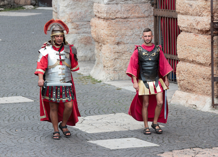 Verona, Italy, September 27, 2015 : Two men dressed in the form of Roman legionaries walk around the Piazza Bra square near the Arena in Verona, Italy