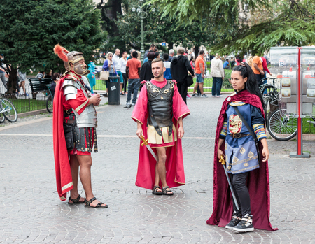 Verona, Italy, September 27, 2015 : Two men and one woman dressed in the form of Roman legionaries stand at the Piazza Bra square near the Arena in Verona, Italy