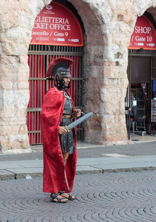 Verona, Italy, September 27, 2015 : One man dressed in the form of Roman legionaries stands at the Piazza Bra square near the Arena in Verona, Italy