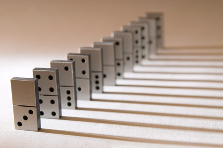 Row of black and white domino pieces with light from the left side and long shadows to the right