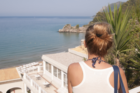 Girl is looking to the distance from the balcony of calm hotel of Corfu island, Greece Stock Photo