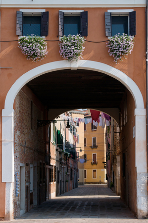 House facade with balcony full of flowers and archway in Venice