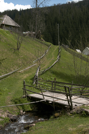 Old wooden house and fence on a green mountain hill, Carpathians Mountains