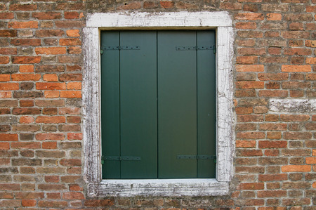 Window with closed shutters on a old brick wall Stock Photo