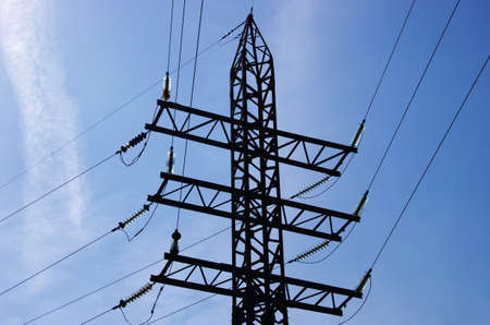 Electricity pylon with insulators and power lines. Blue sky background. Rusty weathered metal