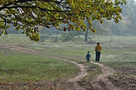 haze: the grandmother on walk with the grandson in the wood, a foggy haze fall