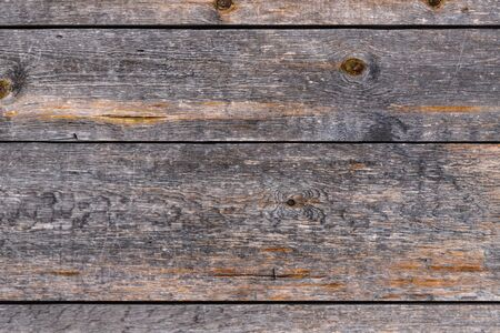 Outdoor wooden flooring from the planks. Knots, scratches and black lines between the boards. Texture for background.