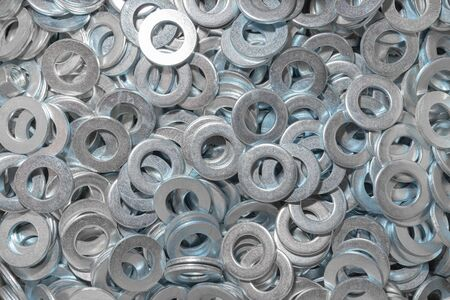 Washers for the bolt. Texture. Many washers for bolts and screws. Background for wallpaper. Shim. Spacer.