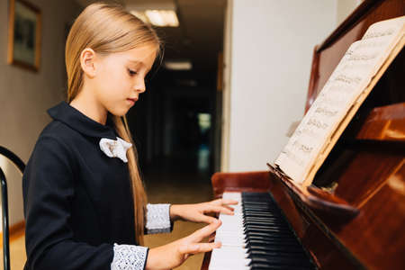 Little girl in a black dress learns to play the piano. The child plays a musical instrument.