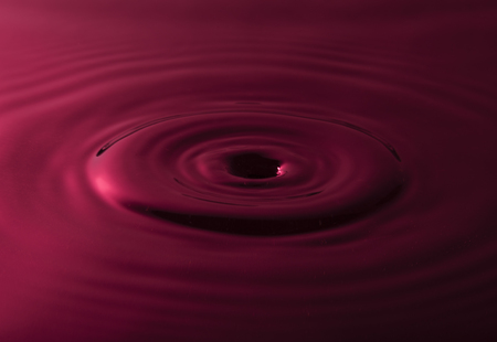 Water drop falling into water making a black hole Stock Photo