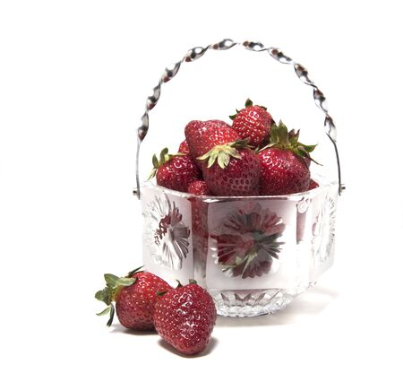Strawberries in a crystal vase two of its next to a vase