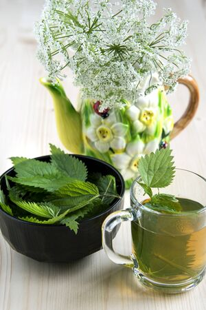 Nettle tea on a wooden table and wild flowers