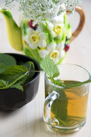 Nettle tea on a wooden table and wild flowers in a ceramic kettle