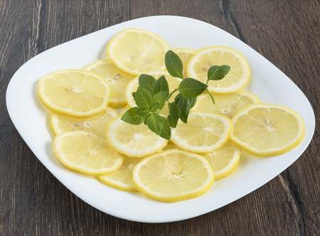 lemon wedge: Lemon slices and mint leaves on a plate Stock Photo