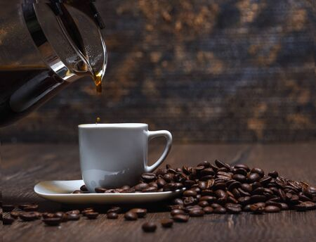 Coffee is pouring into a cup. Coffee beans Stock Photo