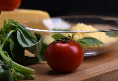 Tomato with basil, cheese in the backgroundon a cutting board