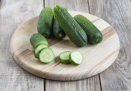 Several whole fresh cucumber and slices of cucumber on a cutting Stock Photo