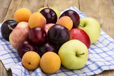 Fruit on a kitchen towel, apples, plums, apricots Rustic stile Archivio Fotografico
