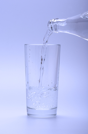 Mineral cold water pouring into the glass from the bottle