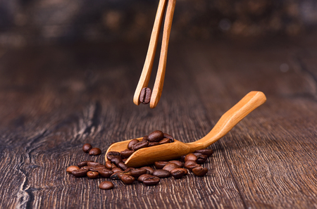 Coffee bean in wooden tweezers. Coffee beans in a wooden ladle. Sorting coffee beans.