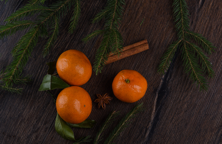 Spruce branches, tangerines and star anise on a wooden background. Rustic style Stock Photo