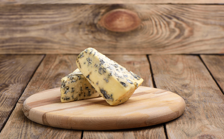 Cheese with blue mold on a cutting board on a wooden background. Close up Reklamní fotografie