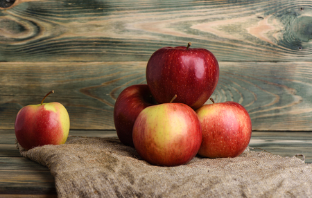 Apples on a coarse cloth on a wooden table. Rustic style. Copy space
