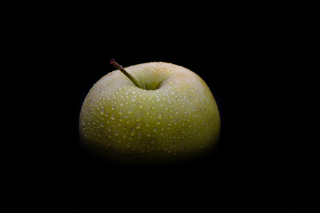 Top of a green ripe apple in drops of water on a black background. Copy space
