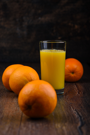 Soft focus. Orange juice in a glass and whole oranges on a wooden background. Rustic style Фото со стока