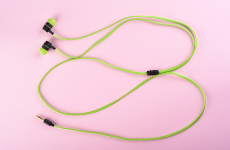 Green headphones or earphones isolated on a pink background Reklamní fotografie - 118978032