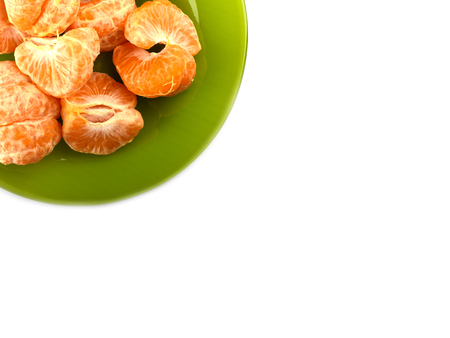 Peeled slices of tangerines on a green plate on a white background. Copy space. Border design