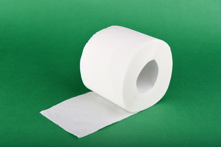 Roll of toilet paper isolated on green background. Copy space