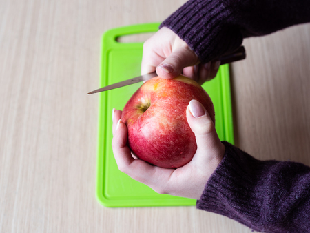 Girl cleans the apple with a knife. Healthy food. Close up